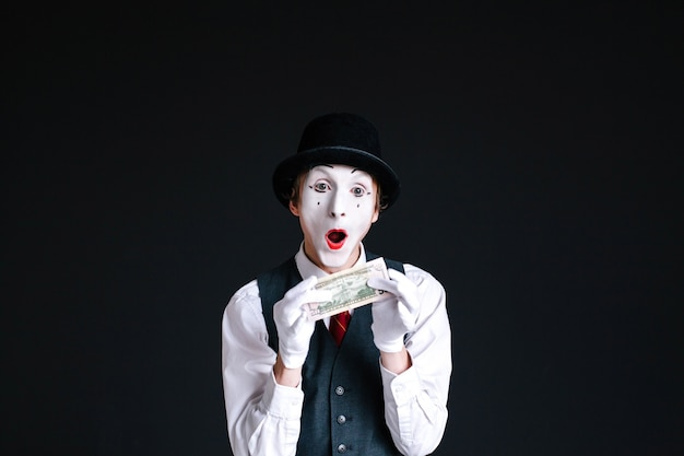 Mime holds dollar in his hands