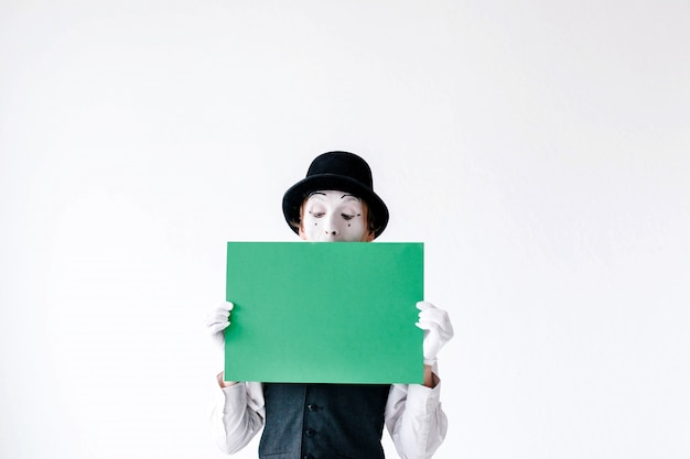 Mime holds green paper before his face