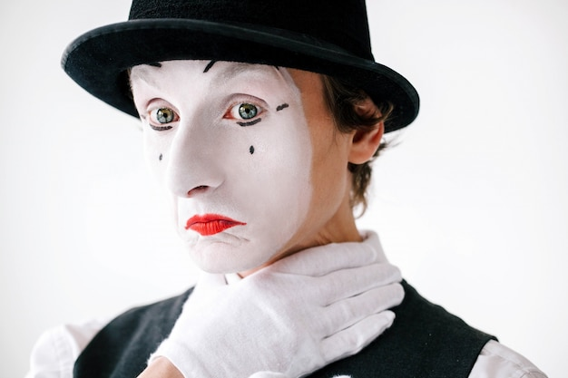 Mime holds hand on his neck