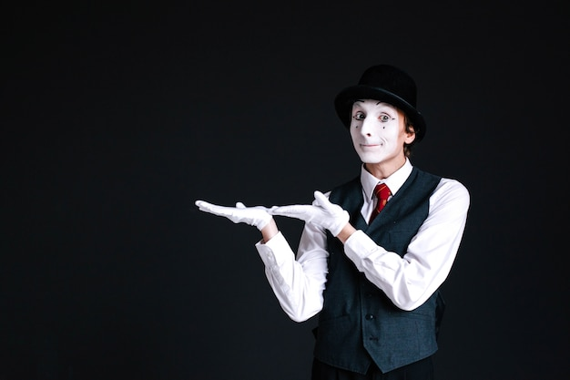 Mime holds something invisible on his palms