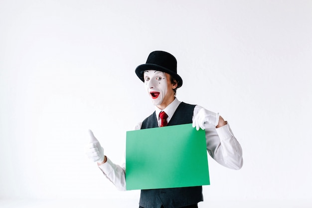 Mime holds thumb up before a green card