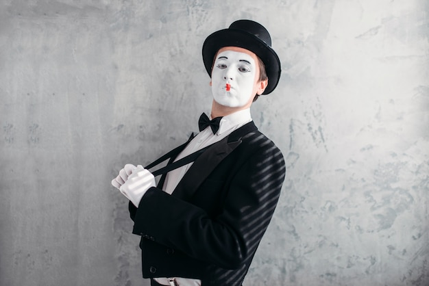 Mime male artist with white makeup mask. comedy actor in suit, gloves and hat.