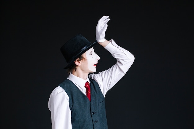 Mime raises his hand up posing on black background