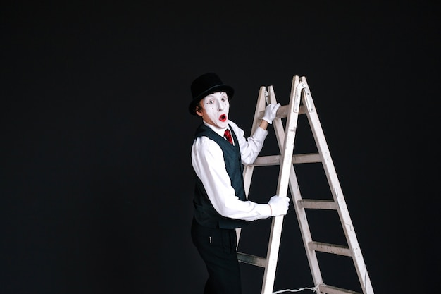 Mime stands on white ladder