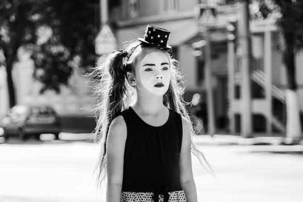 悲しい少女mimeが街の道路に立っています。