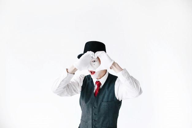 黒い帽子の中のmimeは心を作っている彼の指を見ている