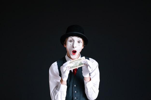 Mimeは彼の手にドルを保持する