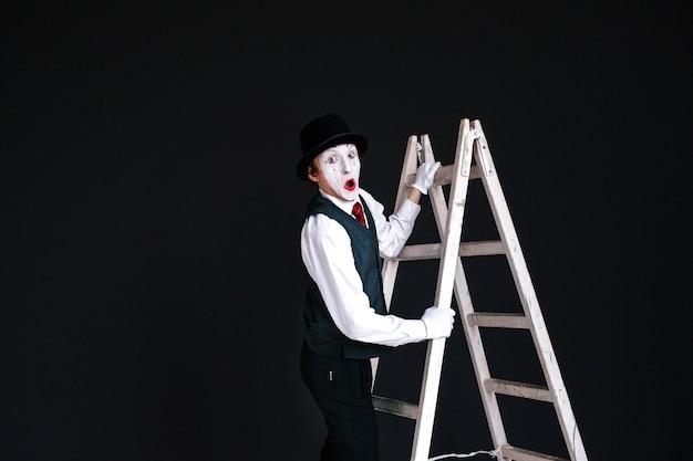 Mimeは白いはしごに立つ