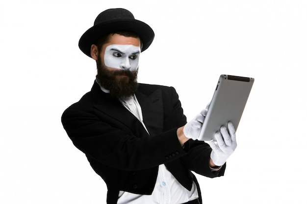 ラップトップに取り組んで顔mimeを持つ男