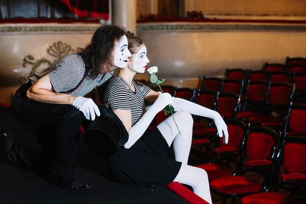 観客のカップルのmimeアーティストは、講堂の舞台に座って