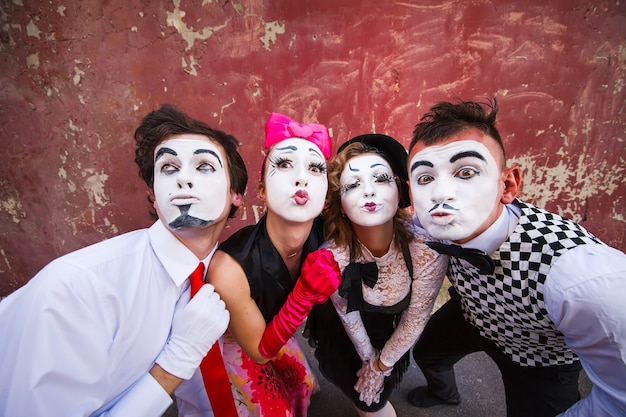 Mimes standing on a red wall