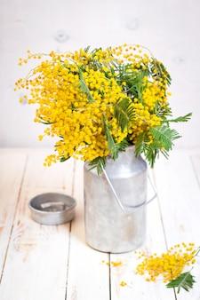 빈티지 금속 우유에 미모사 꽃은 소박한 흰색 나무 바탕에 수 있습니다.