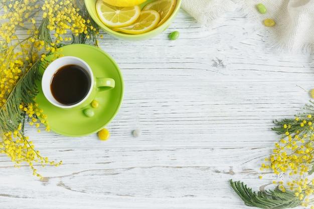 軽い木製のテーブルにミモザ、レモン、コーヒー