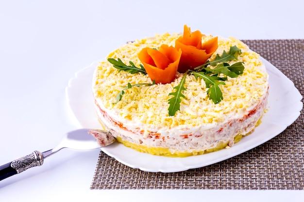 Салат мимоза и ложка на белой тарелке и циновке.