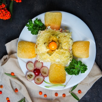 Mimosa salad with chips, fruits, herbs in a plate