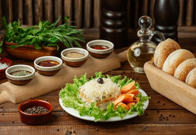 グリーンサラダの葉の内側の上に細かく刻んだホラデンチーズのミモザサラダ