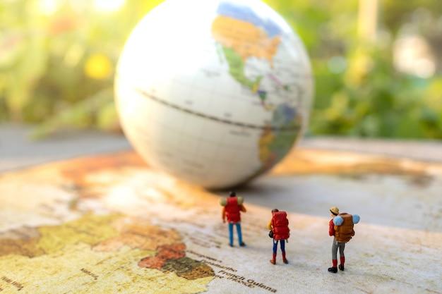 Миниатюрные люди: путешествовать с рюкзаком, стоящим на винтажной карте мира, концепции путешествий и лета.