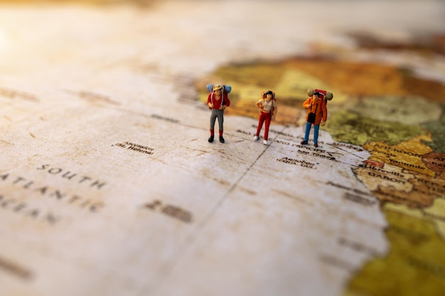 Minature people: traveling with a backpack standing on vintage world map, travel and summer concept.