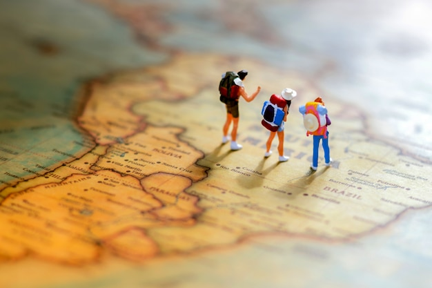 Minature people: traveling with a backpack standing on world map.