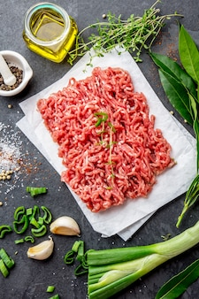 Mince. ground meat with ingredients for cooking on black background. minced beef meat.