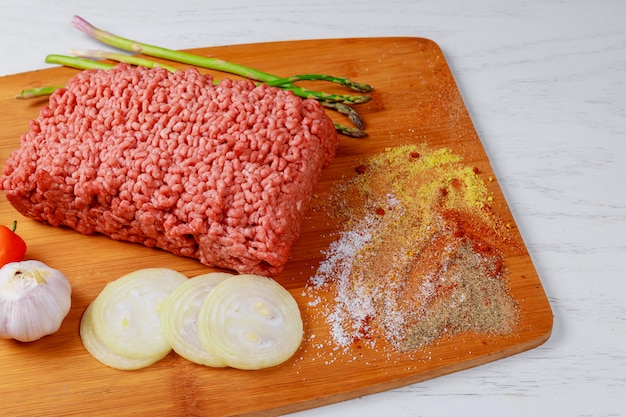 Mince. ground meat with ingredients for cooking on black background