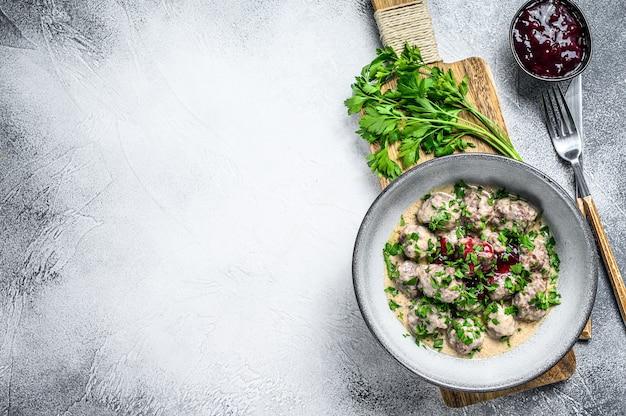 На тарелке фаршировать тефтели со сливочным соусом.