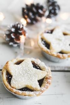 Пирог с фаршем, популярный рождественский десерт, подается на деревянном столе с декоративными огнями и сосновыми шишками
