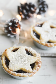 Mince pie, popular christmas dessert, served on wooden table with decorative lights and pine cones