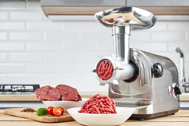 Mince with electric meat grinder in the kitchen