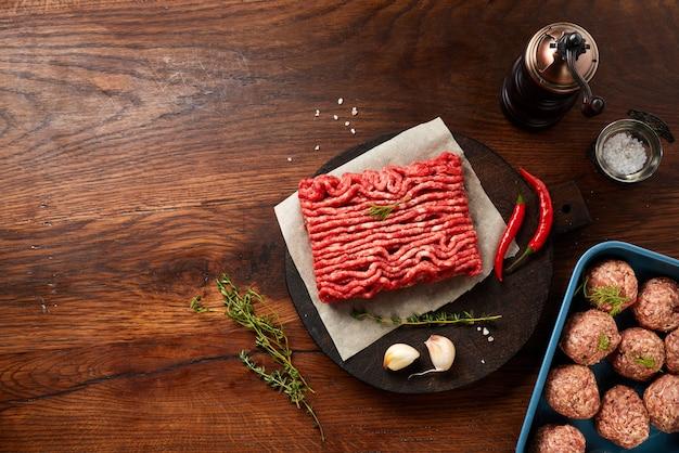 Фарш из говядины и фрикадельки с солью, чесноком, зеленью на деревянный стол.