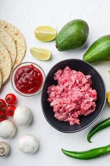 Фарш из говядины с сырыми ингредиентами для тако с кукурузными лепешками, чили, авокадо, на белом фоне. вид сверху.
