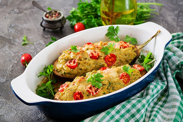 Minced meat chicken and vegetables stuffed eggplants on a grey background