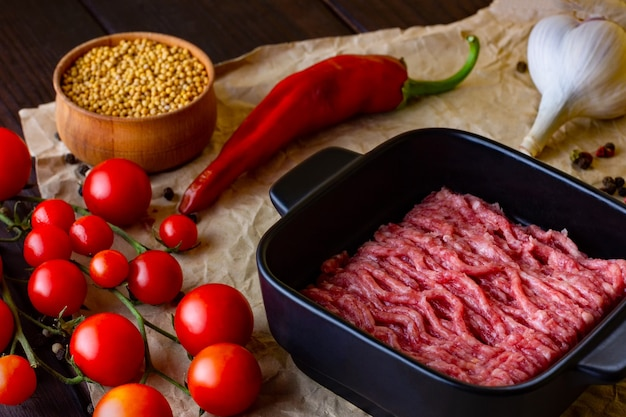Minced meat on craft paper which lies on a wooden light table red hot chili peppers together with pe...