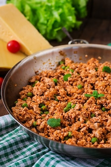 Minced meat in a frying pan for stuffing lasagna.