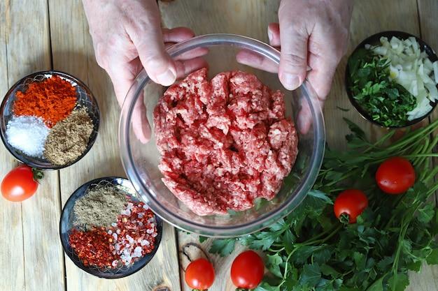 ボウルにひき肉と料理人の手
