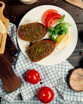 Рубленое мясо в хлебе, помидоры и ломтики лимона