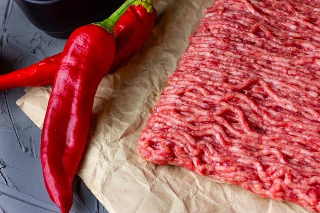 木製のライトテーブルの上にあるクラフト紙のひき肉と赤唐辛子のペ...