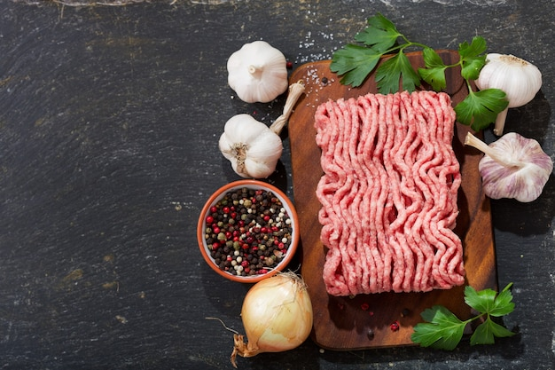 Minced meat with ingredients for cooking on wooden board, top view
