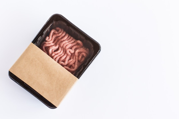 Minced pork meat in vacuum plastic packaging on a white background. top view. logo layout design.