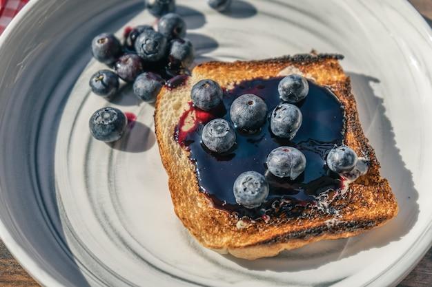 신선한 블루베리와 블루베리 잼을 곁들인 풍부한 빵 토스트의 다진 전망. 건강하고 자연스러운 아침 식사 개념입니다.