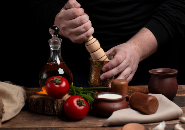 Mincing spices with wooden rolling pin on the table with vegetables