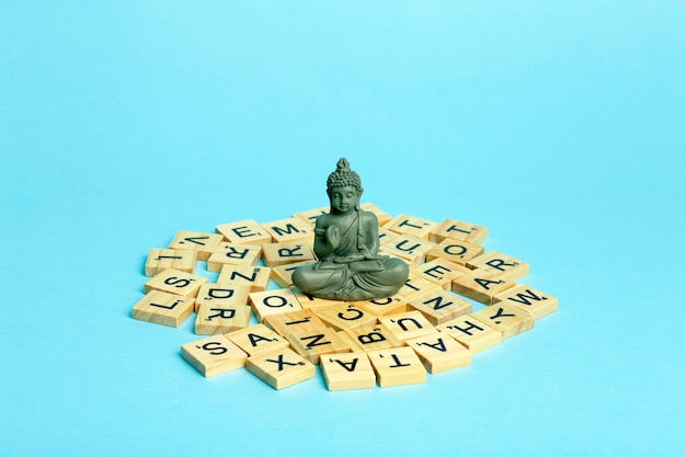 Mind concept. a meditating figure sits on a pile of different letters. the concept of thinking, mind, development and creativity