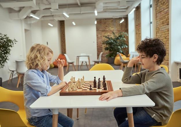 학교 탁자에 앉아 체스를 두는 똑똑한 두 소년의 스포츠 측면 보기