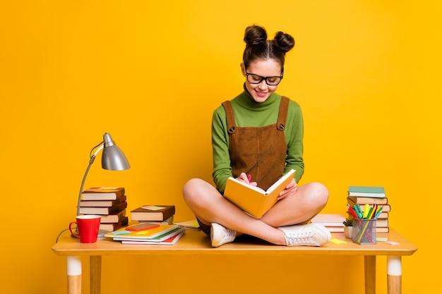 마음을 가진 소녀 앉아 테이블 노란색 배경에 책을 읽고