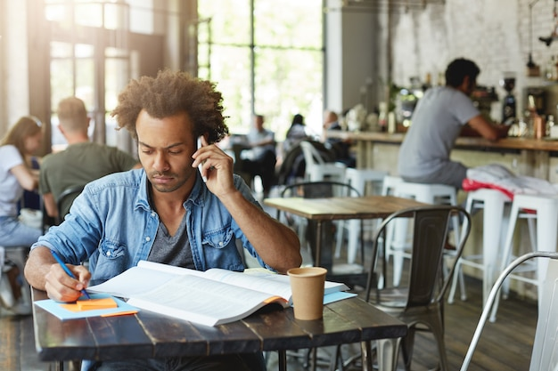 Mindful dark-skinned male student wearing casual clothing preparing for exams sitting at cafe table, reading information in textbook and talking on phone