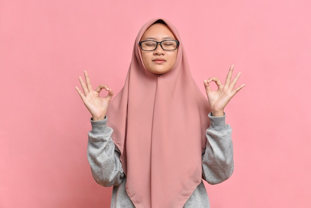 사려 깊은 평화로운 아시아 이슬람 여성은 실내에서 명상하고, 손을 무드라 제스처로 유지하고, 눈을 감고, 긴장을 풀고, 요가 기호에 손가락을 잡고, 분홍색 배경에 격리되어 있습니다.