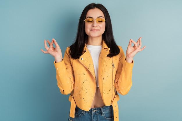 Внимательная, мирная женщина медитирует в помещении, держит руки в жесте мудры, закрывает глаза, пытается расслабиться после долгих часов работы.