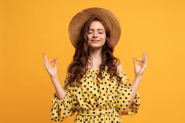 Mindful peaceful woman meditates indoor, keeps hands in mudra gesture, has eyes closed