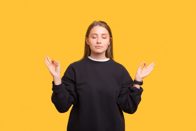 Mindful young woman is standing in zen, serious over yellow background.