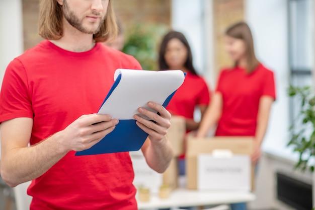 마음 챙김. 실내 뒤에 상자와 함께 서있는 동일한 티셔츠에 문서와 자원 봉사 소녀를 공부하는 세심한 남자
